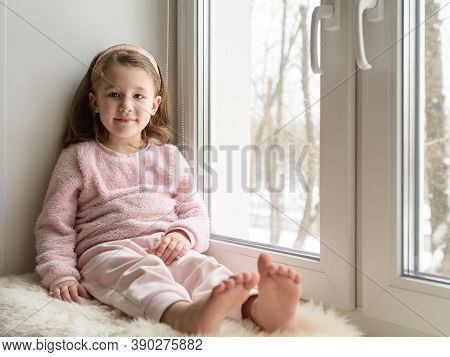 Kid Sitting By Window Looks At Camera Indoor, Portrait Of Pretty Little Girl On Fur Rug On Room Sill