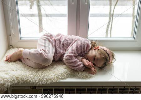 Kid Lies On Fur Rug On Windowsill At Home, Little Girl Dreams Inside House In Winter. Child Sleeps O