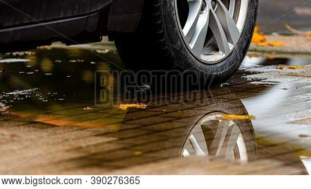 Puddle On The Pavement With A Reflection Of The Car Wheel And Colorful Autumn Leaves