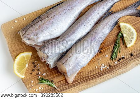 Raw Fresh Pollock Fish On A Wooden Board With Lemon, Salt And Pepper. Top View