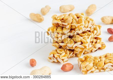 Traditional Peanut Brittle Candy Pieces (gozinaki, Kozinaki) On A White Wooden Background