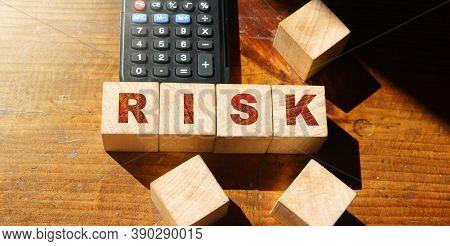 Risk Word Written On Wooden Cubes And Calculator. Financial Risk Assessment, Risk Reward And Portfol