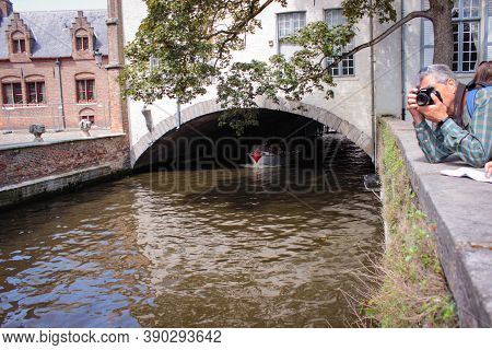 Bruges, Belgium - May 12, 2018:  A Tourist Boat Sails Under A Stone House
