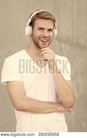 Wireless Earpiece. Handsome Guy Wear Headphones Grey Background. Man Student Listen Modern Music. Mo
