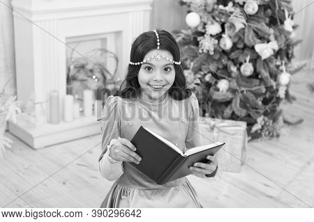 Must Read For Christmas Season. Happy Small Child Read Book By Xmas Tree. Adorable Little Girl Read