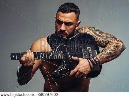 Guitar As Weapon. Brutal Latino Man Playing The Broken Guitar. Hispanic Guitarist Performing Music O