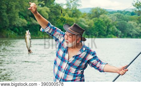 Fishing. Handsome Fisherman Fishing In A River With A Fishing Rod. Man Fisherman Catches A Fish