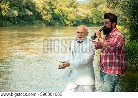 Fisherman Fishing In A River With A Fishing Rod. Difference Between Fly Fishing And Regular Fishing.