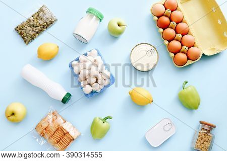 Set Of Grocery Items From Canned Food, Vegetables, Cereal On Blue Background. Food Delivery Concept.