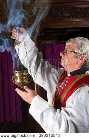 Priest in red chasuble burning incense during mass