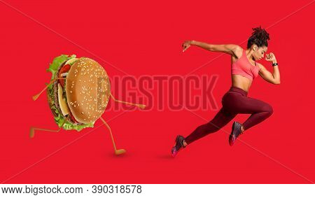 Fit Black Woman Running Away From Burger Losing Weight Exercising Over Red Studio Background. Junk F