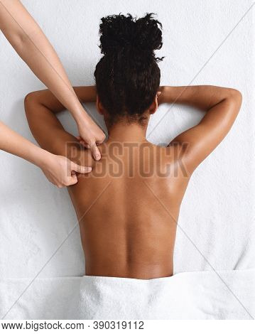 African American Naked Woman Getting Relaxing Back Massage On White, View Above. Top View Of Black L