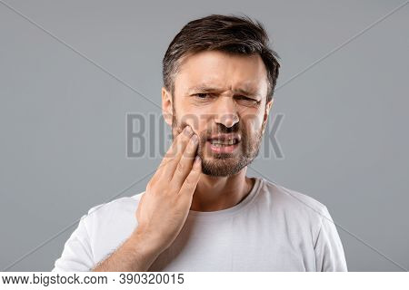 Teeth Problem. Man Suffering From Strong Tooth Pain, Grey Studio Background, Copy Space. Upset Middl