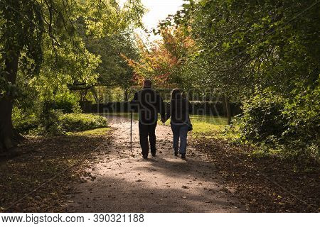 Hexthorpe, Doncaster, England - October 7, 2020. Man Leaning On A Wooden Crutch Walking Hand In Hand