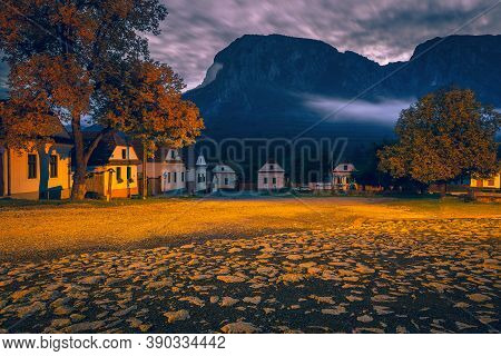 Beautiful Rural Street With Traditional Houses In Row At Dawn. Torocko Village And Stunning Piatra S