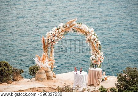 The Round Wedding Arch Is Decorated With A Variety Of Flowers For Beach Ceremony Against The Sea Lan