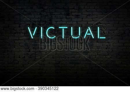 Neon Sign With Inscription Victual Against Brick Wall. Night View