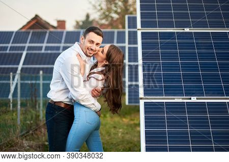 Happy Couple Are Hugging Against The Background Of A Row Of Solar Panels At A Site Near The House. W