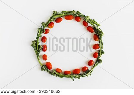 Cherry Tomato And Broccoli Florets Wreath On White Background, Top View. Plant Based Diet Concept