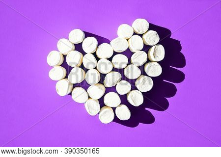 Small White Marshmallows Scattered On A Blue Background With Copy Space, Heart From Marshmallows Top