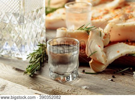 Frozen Glass With Cold Vodka And Slices Of Spicy Salted Lard. Lard With Spices And Herbs On A Old Wo