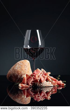 Prosciutto With Ciabatta, Red Wine And Thyme On A Black Reflective Background.