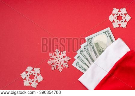Money American Hundred Dollar Bills In Santa Claus Hat On Red Background With Snowflakes