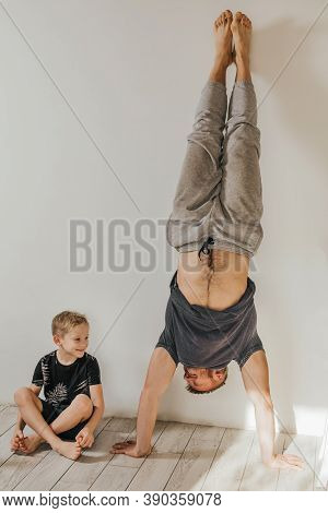 Father And Son Go In For Sports At Home. The Man Is Standing In A Handstand. The Boy Sits And Smiles