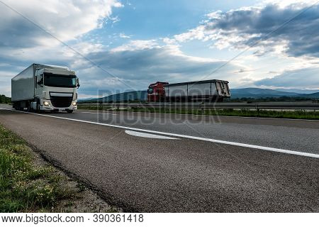 White Semi Trailer Lorry Truck Passing Another Truck On A Highway Driving At Beautiful Dramatic Suns