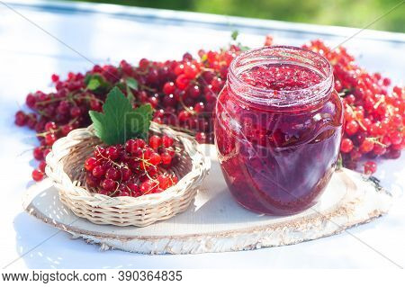 Red, Juicy Berries Of Red Currants And Jars Of Berry Jam On A Wooden Table, Harvest And Cooking Them