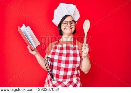 Brunette woman with down syndrome wearing professional baker apron reading cooking recipe book smiling with a happy and cool smile on face. showing teeth.