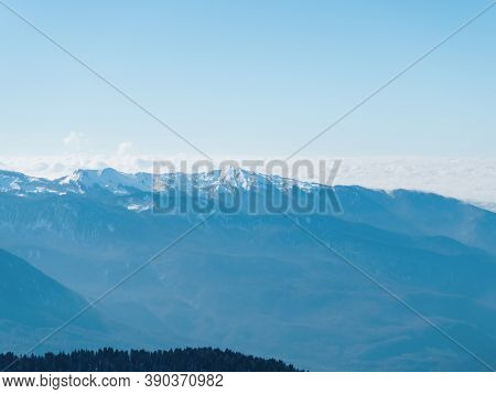 Mountain Valley With Snow Peaks And Clouds At The Summit Level Against Clear Sky