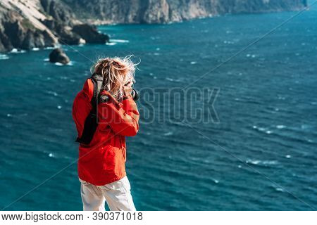 Traveler Photographer In Red Jacket Taking Photo Of Seascape On Camera, Rear View. Tourist Traveler