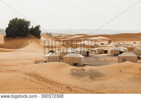 Contemporary Luxury Glamping Camp In Morocco Sahara Desert. Sand Dunes Around. Many White Modern Eco