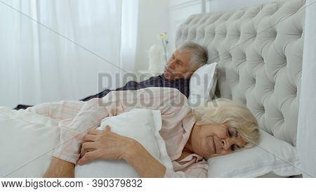 Senior Caucasian Grandparents Couple Lying And Sleeping In Bed At Home. Irritated Woman Getting Dist