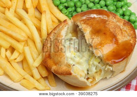 Chicken and vegetable pie with fries, peas and gravy.