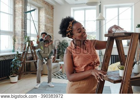 Happy young housewife of African ethnicity cleaning wooden shelves with duster during domestic chores while her husband playing with little son