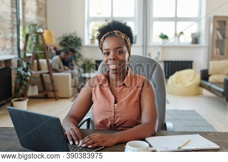 Smiling young African female freelancer looking at you during work in front of laptop while sitting in armchair by table in front of camera