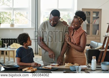 Young African man preparing sandwiches for breakfast while standing by table surrounded by his affectionate wife and their adorable little son