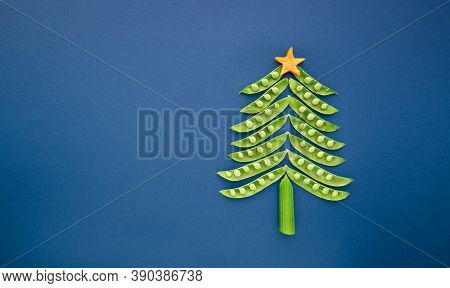 Vegans Christmas Tree Made Of Green Peas On Blue Background