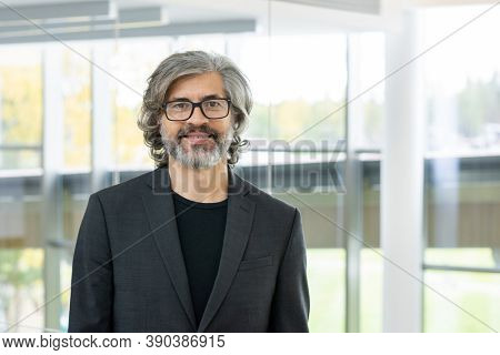 Cheerful mature bearded businessman or director of company standing in front of camera against large window and looking at you with smile