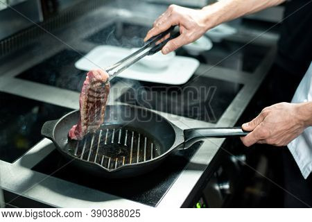 Hands of young chef holding half-roasted piece of meat over hot grill frying pan with vegetable oil while standing by electric stove