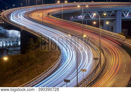 Highway At Night Lights. Fast Car Light Path, Trails And Streaks On Interchange Bridge Road. Night L