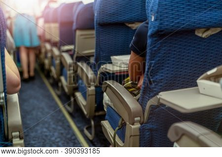 Passenger Inside Economy Seat Of Commercial Airplane. Plane Cabin Interior. Blur Stewardess Or Air H