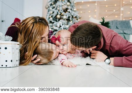 The Dad, Mom Kiss Little Son And Daughter With Gifts Lying On Floor Near Christmas Tree. Happy New Y