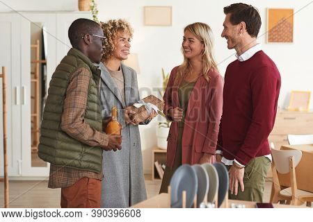 Multi-ethnic Group Of Elegant Adult People Greeting Each Other And Exchanging Gifts While Welcoming