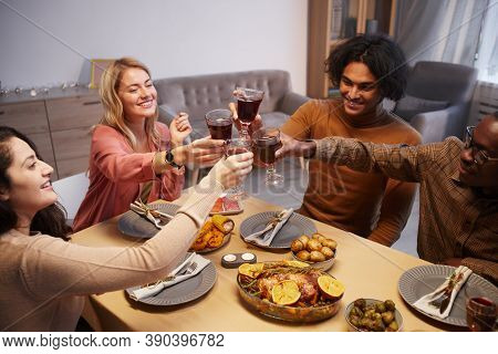 High Angle View At Multi Ethnic Group Of Happy People Toasting While Enjoying Dinner Party With Frie