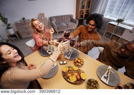 High Angle View At Multi Ethnic Group Of Cheerful Young People Toasting While Enjoying Dinner Party