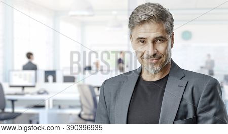 Business portrait - confident businessman in office. Trustworthy older man in his 50s with gray hair. Copy space.