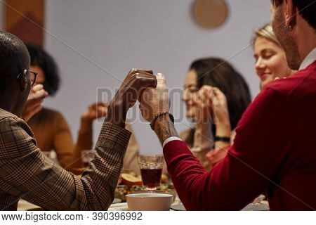 Multi-ethnic Group Of People Holding Hands In Prayer At Thanksgiving Dinner With Friends And Family,